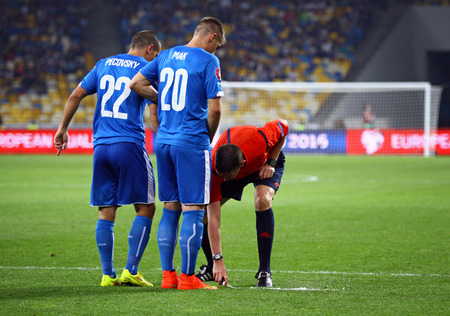 KYIV, UKRAINE - SEPTEMBER 8, 2014: Referee Craig Thomson of Scotland uses the vanishing foam during UEFA EURO 2016 Qualifying game between Ukraine and Slovakia