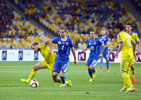 gusev: KYIV, UKRAINE - SEPTEMBER 8, 2014: Oleh Gusev of Ukraine (L) fights for a ball with Peter Pekarik of Slovakia during their UEFA EURO 2016 Qualifying game