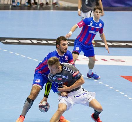 KYIV, UKRAINE - OCTOBER 18, 2014: Havard Tvedten of Aalborg (in grey) fights for a ball with Mykola Stetsyura of Motor during their European Handball Champions League game