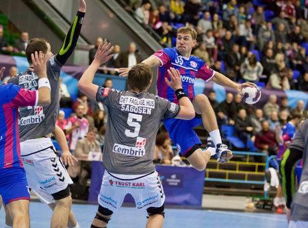 KYIV, UKRAINE - OCTOBER 18, 2014: Sergiy Onufrienko of Motor (in Red-Blue) attacks during European Handball Champions League game against Aalborg