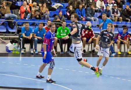 KYIV, UKRAINE - OCTOBER 18, 2014: Simon Hald Jensen of Aalborg (C) attacks during European Handball Champions League game against Motor
