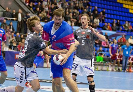 KYIV, UKRAINE - OCTOBER 18, 2014: Sergii Burka of Motor (in Red-Blue) attacks during European Handball Champions League game against Aalborg Editorial