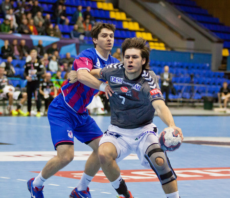 KYIV, UKRAINE - OCTOBER 18, 2014: Oleg Skopintsev of Motor (L) fights for a ball with Martin Larsen of Aalborg during their European Handball Champions League game