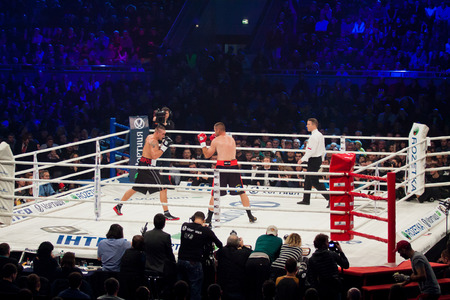 KYIV, UKRAINE - DECEMBER 13, 2014: Oleksandr Usyk of Ukraine (white-black shorts) and Danie Venter of South Africa in the ring during WBO Intercontinental Cruiserweight Title fight