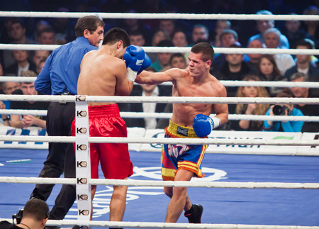 mikhail: KYIV, UKRAINE - DECEMBER 13, 2014: Eldos Sarkulov of Kazakhstan (in red) fights with Mikhail Andriets of Ukraine during Evening of Boxing in the Palace of Sports in Kyiv Editorial