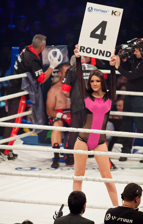 show ring: KYIV, UKRAINE - DECEMBER 13, 2014: Boxing ring girl holding a board with round number during WBO Intercontinental cruiserweight Title fight Oleksandr Usyk vs Danie Venter