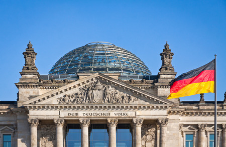 Flag of Federal Republic of Germany waving in front of the German parliament building Reichstag in Berlin Germany Banco de Imagens