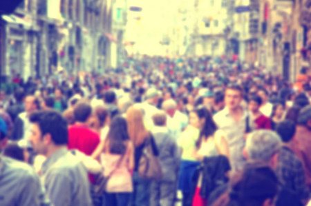 Background with unrecognizable blurred people walking on the street.