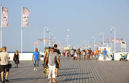 longest: SOPOT POLAND  JULY 26 2012: Tourists walking along the pier in Sopot city. Built in 1827 this 511.5m pier is the longest wooden pier in Europe