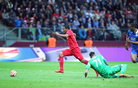 bacca: WARSAW, POLAND - MAY 27, 2015: Carlos Bacca in Red of FC Sevilla scores a goal during UEFA Europa League Final game against FC Dnipro at Warsaw National Stadium