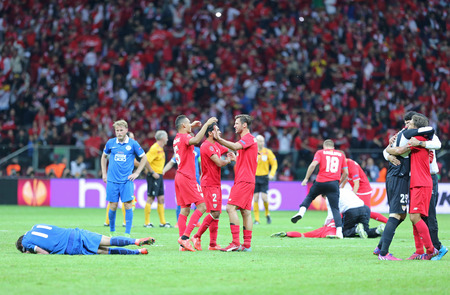 react: WARSAW, POLAND - MAY 27, 2015: FC Sevilla players in Red react after winning UEFA Europa League Final in game against FC Dnipro at Warsaw National Stadium