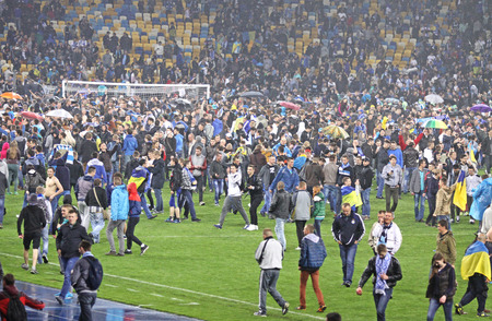 winning pitch: KYIV, UKRAINE - MAY 14, 2015: FC Dnipro supporters run out into the pitch to celebrate the winning after UEFA Europa League semifinal game against Napoli at NSK Olimpiyskyi stadium Editorial