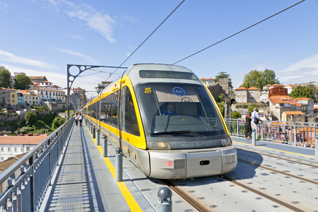 douro: PORTO, PORTUGAL - JUNE 17, 2013: Light rail train of Metro do Porto, part of the public transport system of Porto city. First line of the system was opened in 2002