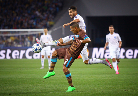 maxi: KYIV, UKRAINE - SEPTEMBER 16, 2015: Miguel Veloso of Dynamo Kyiv in White fights for a ball with Maxi Pereira of FC Porto during their UEFA Champions League game at NSC Olimpiyskyi stadium
