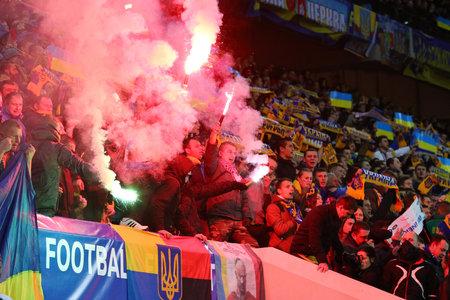 ultras: LVIV, UKRAINE - NOVEMBER 14, 2015: Ukrainian ultra supporters ultras burn flares during UEFA EURO 2016 Play-off for Final Tournament game between Ukraine and Slovenia at Lviv Arena