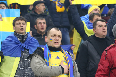 anthem: LVIV, UKRAINE - NOVEMBER 14, 2015: Ukrainian supporters sing the national anthem during UEFA EURO 2016 Play-off for Final Tournament game between Ukraine and Slovenia at Lviv Arena Editorial