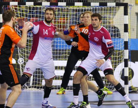 balonmano: Kiev, Ucrania - 28 de noviembre de 2015: jugadores de balonmano Kadetten Schaffhausen en el control de naranja en un balón durante la VELUX EHF Champions League de balonmano contra 201.516 Motor
