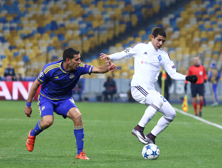 maccabi: KYIV, UKRAINE - DECEMBER 9, 2015: Derlis Gonzalez of Dynamo Kyiv R fights for a ball with Eytan Tibi of Maccabi Tel-Aviv during their UEFA Champions League game at NSC Olimpiyskyi stadium