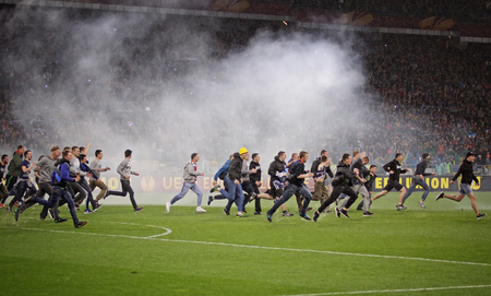 winning pitch: KYIV, UKRAINE - MAY 14, 2015: FC Dnipro ultra supporters run out into the pitch with flare to celebrate victory after UEFA Europa League semifinal game against SSC Napoli at NSK Olimpiyskyi stadium