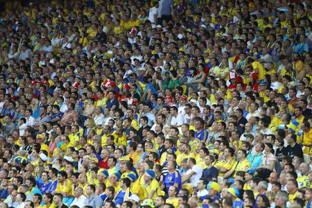 KYIV, UKRAINE - JUNE 11, 2012: People watch the UEFA EURO 2012 football game between Ukraine and Sweden at Olympic stadium in Kyiv