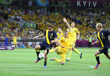 gusev: KYIV, UKRAINE - JUNE 11, 2012: Johan Elmander of Sweden 11 fights for a ball with Oleh Gusev 9 of Ukraine during their UEFA EURO 2012 game at Olympic stadium in Kyiv