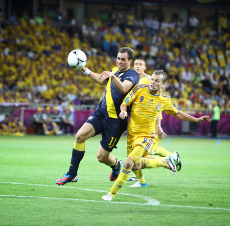 9 ball: KYIV, UKRAINE - JUNE 11, 2012: Johan Elmander of Sweden 11 fights for a ball with Oleh Gusev 9 of Ukraine during their UEFA EURO 2012 game at Olympic stadium in Kyiv