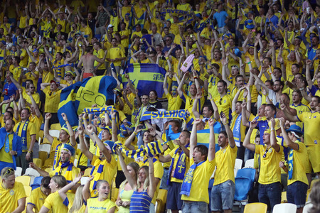 olimpiysky: KYIV, UKRAINE - JUNE 11, 2012: Swedish football supporters show their support during UEFA EURO 2012 game against Ukraine at Olympic stadium in Kyiv Editorial