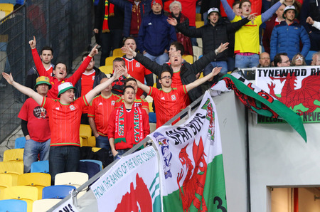 ultras: KYIV, UKRAINE - MARCH 28, 2016: Welsh supporters show their support during Friendly match between Ukraine and Wales at NSC Olympic stadium in Kyiv, Ukraine