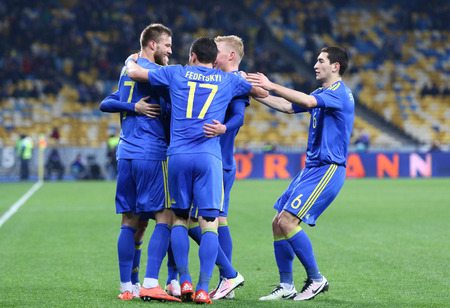react: KYIV, UKRAINE - MARCH 28, 2016: Ukrainian footballers react after scored a goal during Friendly match against Wales at NSC Olympic stadium in Kyiv, Ukraine. Ukraine won 1-0