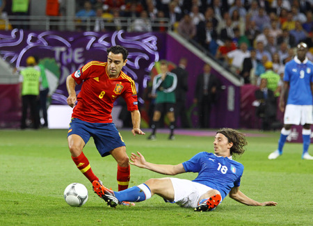 xavi: KYIV, UKRAINE - JULY 1, 2012: Xavi Hernandez of Spain (L) fights for a ball with Riccardo Montolivo of Italy during their UEFA EURO 2012 Final game at Olympic stadium in Kyiv, Ukraine