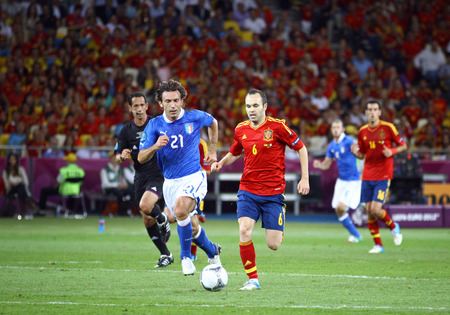 KYIV, UKRAINE - JULY 1, 2012: Andres Iniesta of Spain (in Red) controls a ball during UEFA EURO 2012 Final game against Italy at Olympic stadium in Kyiv, Ukraine