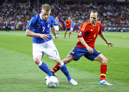 iniesta: KYIV, UKRAINE - JULY 1, 2012: Ignazio Abate of Italy (L) fights for a ball with Andres Iniesta of Spain during their UEFA EURO 2012 Final game at Olympic stadium in Kyiv, Ukraine Editorial