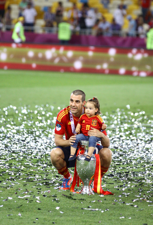 winning pitch: KYIV, UKRAINE - JULY 1, 2012: Alvaro Negredo of Spain poses for a photo with his daughter after UEFA EURO 2012 Final game against Italy at Olympic stadium. Spain won the game and the Tournament