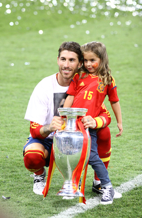 winning pitch: KYIV, UKRAINE - JULY 1, 2012: Sergio Ramos of Spain poses for a photo with his daughter after UEFA EURO 2012 Final game against Italy at Olympic stadium in Kyiv. Spain won the game and the Tournament Editorial