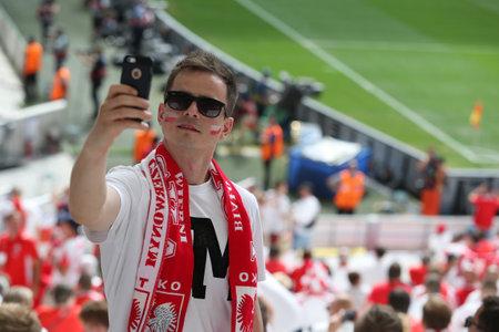 ultras: MARSEILLE, FRANCE - JUNE 21, 2016: Polish fan makes selfie portrait on the smartphone during the UEFA EURO 2016 game Ukraine v Poland at Stade Velodrome in Marseille