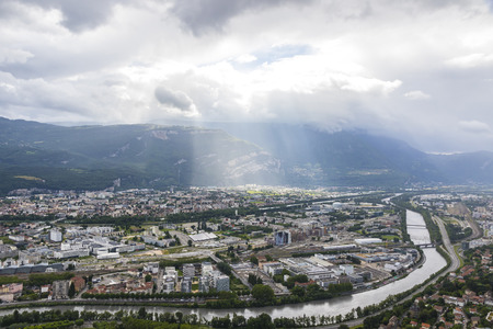 Grenoble city and Isere river, France. Picturesque aerial view from Bastille in summer cloudy day