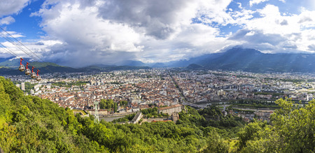 Panorama of Grenoble city and French Alps on the background, Rhone-Alpes region, France. Picturesque aerial view from Bastille in summer cloudy day