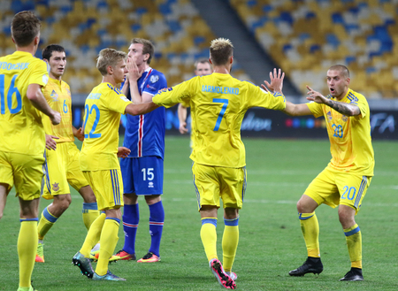 scored: KYIV, UKRAINE - SEPTEMBER 5, 2016: Ukrainian players (in yellow) celebrate after scored a goal during FIFA World Cup 2018 qualifying game against Iceland at NSC Olympic stadium in Kyiv, Ukraine Editorial