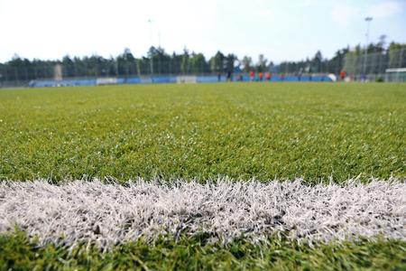 pasto sintetico: Primer plano césped sintético para campo de fútbol (soccer) deporte. Patrón de césped artificial verde. jugadores de fútbol enmascaradas en el fondo