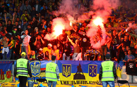 KYIV, UKRAINE - SEPTEMBER 10, 2013: Ukrainian ultra supporters (ultras) burn flares and show their support during FIFA World Cup 2014 qualifier game against England at NSC Olympic stadium in Kyiv