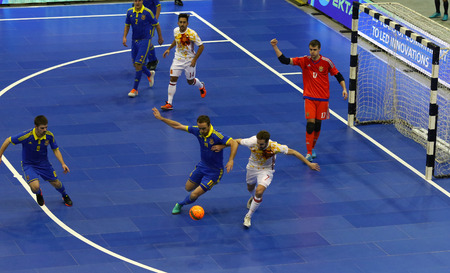 striker: KYIV, UKRAINE - JANUARY 29, 2017: Players of Spain (in White) and Ukraine (in Blue) teams in action during their Friendly Futsal match at Palats of Sports in Kyiv, Ukraine