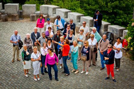 리스본, 포르투갈 -2011 년 6 월 11 일 : 가이드를 듣고 및 리스본에서 Sintra 마을에 위치한 Sintra 궁전 건물 찾고 관광객의 그룹 에디토리얼