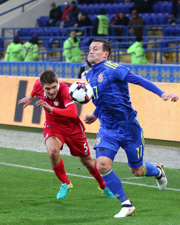 midfielder: Kharkiv, Ukraine - November 15, 2016: Artem Fedetskiy of Ukraine (R) fights for a ball with Aleksandar Ignjovski of Serbia during their Friendly match at Metalist stadium in Kharkiv, Ukraine Editorial