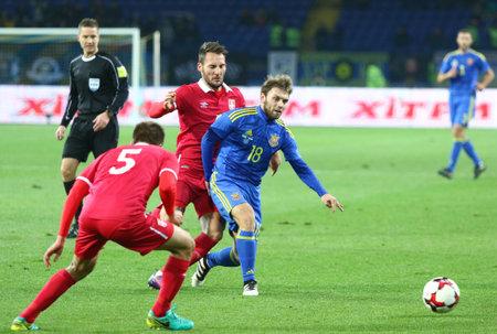 midfielder: Kharkiv, Ukraine - November 15, 2016: Olexandr Karavayev of Ukraine (in Blue) fights for a ball with Serbian players during their Friendly match at Metalist stadium in Kharkiv, Ukraine