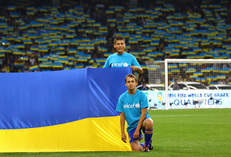 KYIV, UKRAINE - SEPTEMBER 10, 2013: Unrecognisable children hold the flag of Ukraine before the FIFA World Cup 2014 qualifier game Ukraine vs England at NSC Olympic stadium in Kyiv