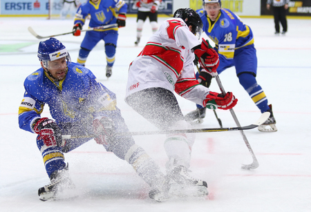 KYIV, UKRAINE - APRIL 22, 2017: Igor KUGUT of Ukraine (L) fights for a puck with Janos HARI of Hungary during their IIHF 2017 Ice Hockey World Championship Div 1 Group A game at Palace of Sports