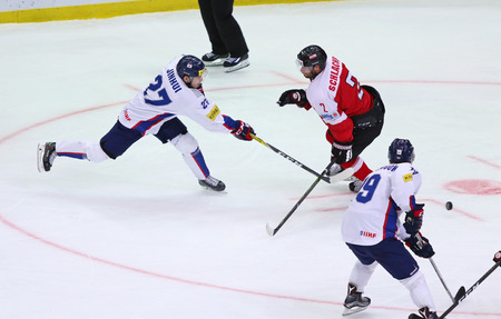 KYIV, UKRAINE - APRIL 27, 2017: Austrian (in Red) and South Korean players fight for a puck during IIHF 2017 Ice Hockey World Championship Div 1 Group A game against South Korea at Palace of Sports