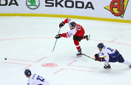 KYIV, UKRAINE - APRIL 27, 2017: Forward Manuel GANAHL of Austria (in Red) shots the puck during the IIHF 2017 Ice Hockey World Championship Div 1A game against South Korea at Palace of Sports in Kyiv