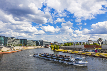 BERLIN, GERMANY - JULY 1, 2014: Sightseeing boats on the river Spree in a sunny summer day in center of Berlin city, Germany. Spreebogenpark on the right. TV-tower and Bundestag roof on the background Editorial