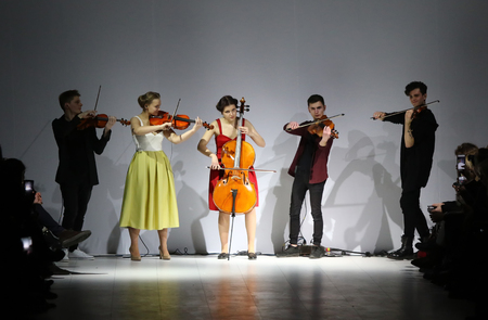 cellos: KYIV, UKRAINE - FEBRUARY 7, 2017: Artists perform on catwalk during the presentation of collection by designer Maryna RYBALKO as part of 40th Ukrainian Fashion Week season AW 201718 in Kyiv, Ukraine